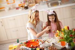 Mother with daughter painting eggs stock photos