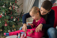 Mother and daughter painting finger nails on xmas day Stock Photo