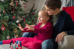 Mother and daughter painting finger nails on xmas day Royalty Free Stock Photography