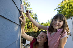 Mother and Daughter Painting a House - Horizontal Stock Image