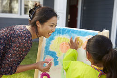 Mother And Daughter Painting Picture In Garden Together Stock Image