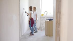 Mother and daughter painting wall. In apartment room. Beautiful family doing repairs in new flat. Woman and teen girl making decorate room, laughing and having stock video