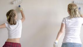 Mother and daughter painting wall. In apartment room. Beautiful family doing repairs in new flat. Funny woman and teen girl having good mood - making decorate stock footage