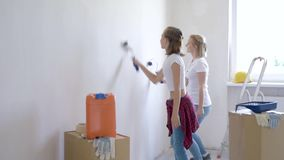 Mother and daughter painting wall. In apartment room. Beautiful family doing repairs in new flat. Funny woman and teen girl having good mood - making decorate stock video footage