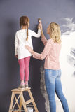 Mother and daughter painting wall Royalty Free Stock Photos