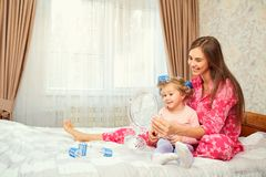 Mother and daughter in pajamas play with a mirror together. Mothers Day Royalty Free Stock Images