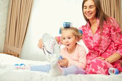 Mother and daughter in pajamas play with a mirror together. Mothers Day Royalty Free Stock Image