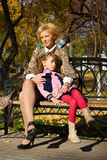 Happy mother and daughter in autumn city park stock image