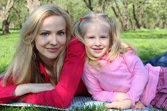 Mother and daughter in park lie on grass Stock Photo