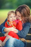 Mother and daughter in the park. Little girl playing with mother in the autumn park Stock Photo