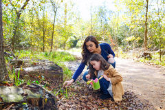 Mother daughter in a park picking clover plants Stock Photo