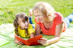 Mother with daughter in park reading book Stock Photography