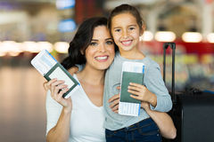 Mother daughter passports. Beautiful mother and daughter holding passports and boarding pass at airport stock images