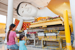 Mother and daughter pay respect to buddha statue. Mother and daughter pay respect to sleeping buddha statue Royalty Free Stock Image
