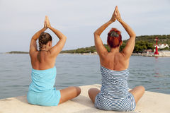Mother and daughter performing joga on sunny beach. Mother and daughter performing joga on beach, sea coast, meditating in yoga pose, on sunny summer day Stock Photos