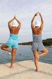Mother and daughter performing joga on sunny beach Stock Photography
