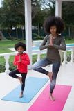 Mother and daughter performing yoga in the porch. At home Stock Images