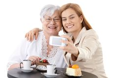 Mother and daughter photographing themselves. Senior mother and young daughter sitting at coffee table, photographing themselves by digital camera, smiling Royalty Free Stock Images