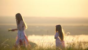 Mother and daughter picking flowers to weave wreath on the hill at sunset stock footage