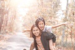 Mother and daughter piggyback ride with mum stock photos