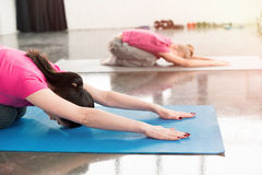 Mother and daughter in pink shirts practicing yoga in hare pose Royalty Free Stock Photos
