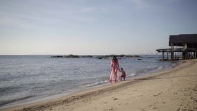 Mother and daughter in pink swimsuits and a long dress are walking along the seashore. concept of a happy family. 4k. stock footage
