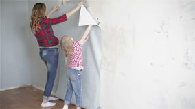 Mother and daughter in a plaid shirt are trying on a new piece of wallpaper to the wall. stock footage