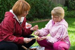 Mother and daughter planting tulips. Family time outside in the garden by planting spring bulbs together into container during autumn Royalty Free Stock Images