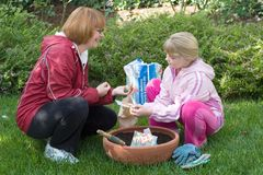 Mother and daughter planting tulips stock images