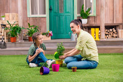 Mother and daughter with plants and flowerpots Stock Photo