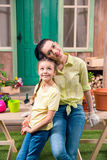 Mother and daughter with plants and flowerpots standing and hugging at table Royalty Free Stock Photography