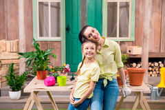 Mother and daughter with plants and flowerpots standing and hugging at table Royalty Free Stock Images