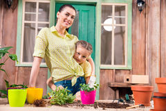 Mother and daughter with plants and flowerpots standing and hugging at table on porch Stock Photography