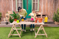 Mother and daughter with plants and flowerpots standing at table Stock Photos