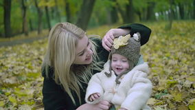 Mother and daughter play in autumn park. Parent and baby walk in the forest on a fall day. Baby playing outdoors with stock video footage