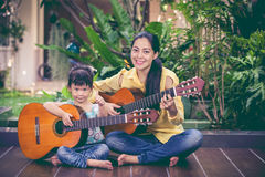 Mother with daughter play guitar. Family spending time together. Happy family spending time together. Asian mother with daughter playing classic guitar at home Stock Photos
