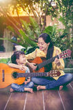 Mother with daughter play guitar. Family spending time together Royalty Free Stock Image