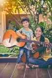 Mother with daughter play guitar. Family spending time together. Happy family spending time together with bright sunlight at home. Asian mother with daughter Stock Photo