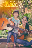 Mother with daughter play guitar. Family spending time together. Happy family spending time together with bright sunlight at home. Asian mother with daughter stock photos