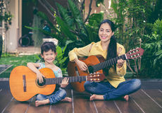 Mother with daughter play guitar. Family spending time together. Happy family spending time together at home. Asian mother with daughter playing classic guitar Stock Image