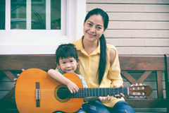 Mother with daughter play guitar. Family spending time together. Happy family spending time together at home. Asian mother with daughter playing classic guitar Stock Photography