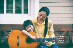 Mother with daughter play guitar. Family spending time together. Happy family spending time together at home. Asian mother with daughter playing classic guitar Royalty Free Stock Photo