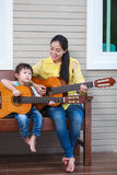 Mother with daughter play guitar. Family spending time together. Happy family spending time together at home. Asian mother with daughter playing classic guitar Stock Photos
