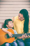 Mother with daughter play guitar. Family spending time together. Happy family spending time together at home. Asian mother with daughter playing classic guitar Stock Images