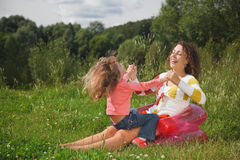 Mother and daughter play in the open air Stock Images