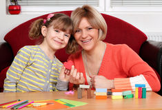 Mother and daughter play with plasticine and make heart Stock Images