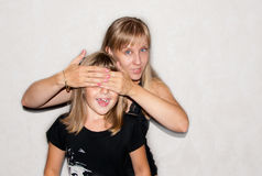 Mother and daughter play quess who. Mother and daughter in black clothes play quess who Stock Image