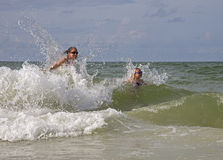 Mother and daughter play in surf. Stock Image