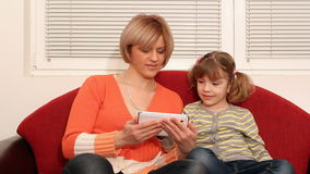 Mother and daughter play with tablet Stock Photography