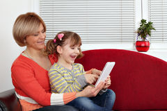 Mother and daughter play with tablet pc Stock Images